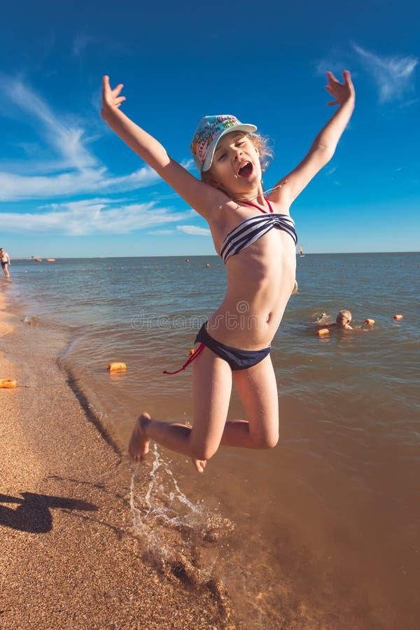 Blondes nettes siebenjähriges Mädchen, das Spaß hat und eine gute Zeit in dem Meer während der Feiertage hat lizenzfreie stockbilder