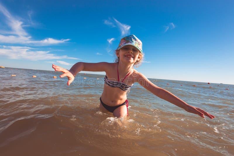 Blondes nettes siebenjähriges Mädchen, das Spaß hat und eine gute Zeit in dem Meer während der Feiertage hat stockbilder