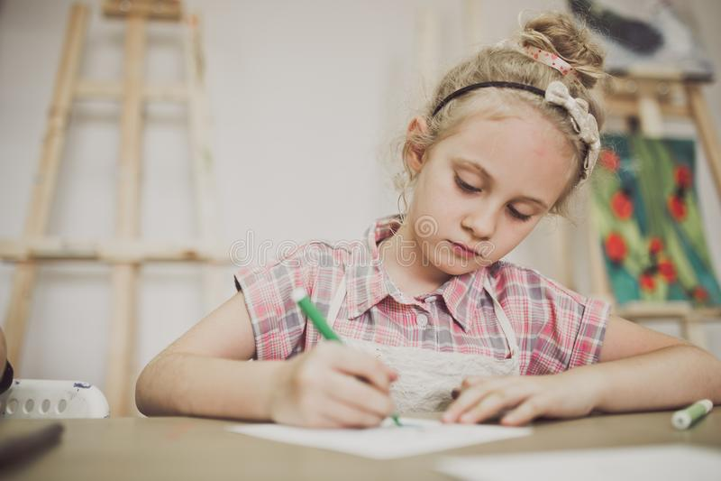 Blondes nettes siebenjähriges Mädchen, zeichnet am Tisch im kreativen Studio lizenzfreies stockfoto