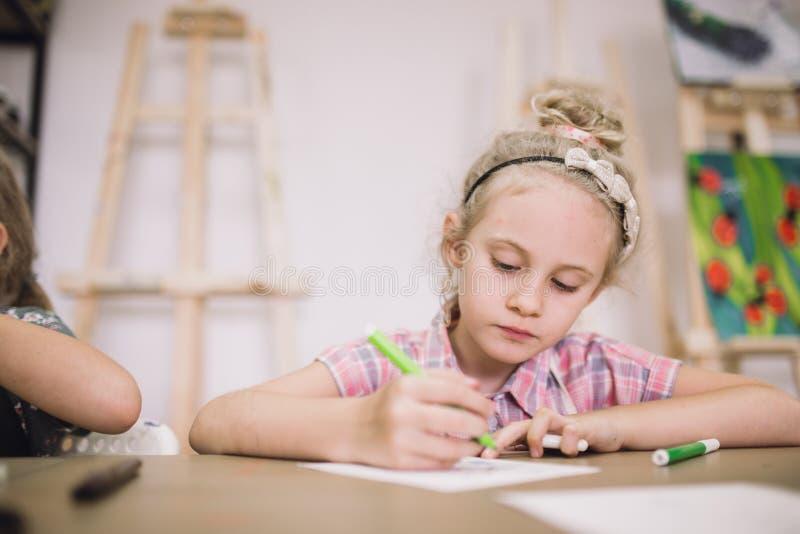 Blondes nettes siebenjähriges Mädchen, zeichnet am Tisch im kreativen Studio lizenzfreie stockfotografie