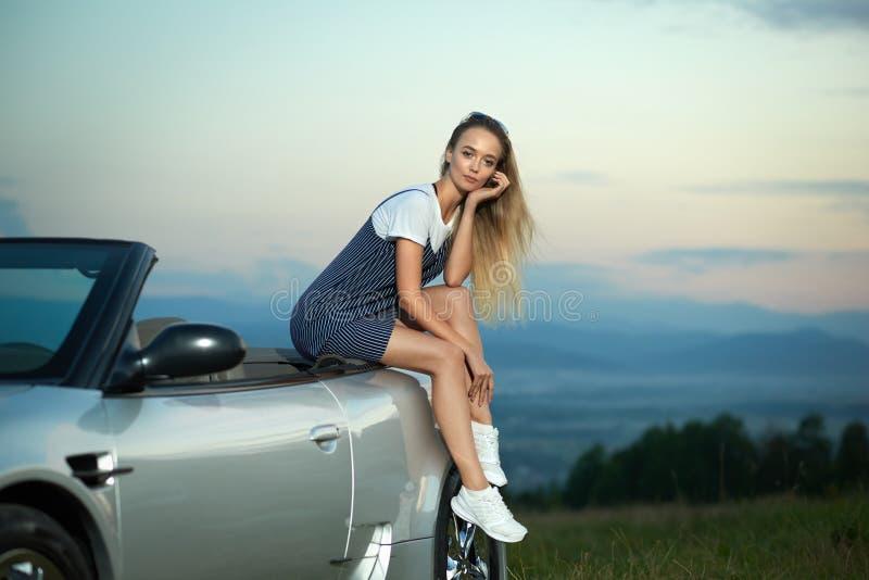 Blondes Sitzen auf luxuriösem silbernem Cabriolet und Aufstellung lizenzfreie stockfotos