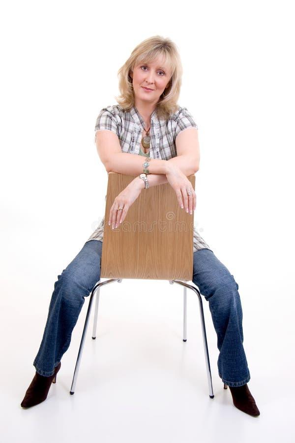Blondes Sitzen auf Stuhl stockfotos