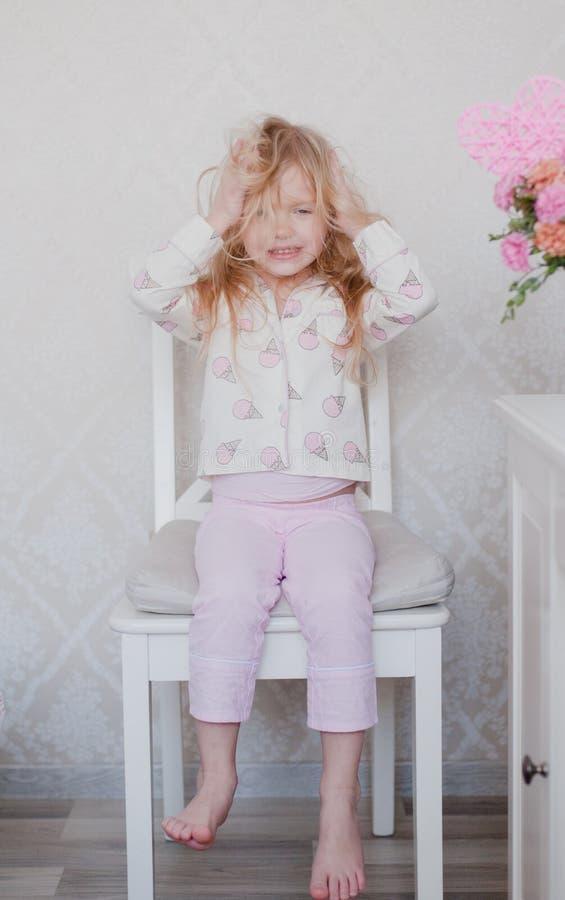 Blondes Sitzen des kleinen Mädchens auf einem Stuhl in ihrer rosa Pyjamaspitze, Chaos auf dem Kopf verursachend stockbild