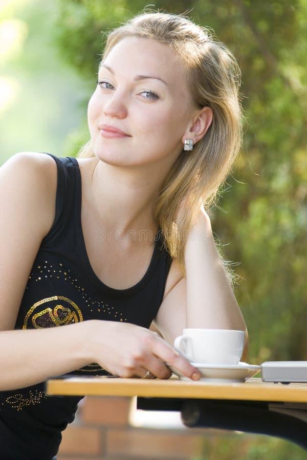 Blondes Sitzen im Straßenkaffee lizenzfreie stockfotografie