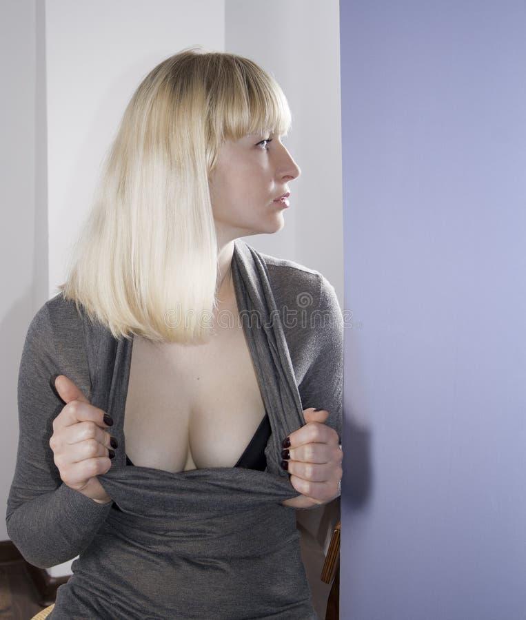 Blondes Tragen der Frau, ihr Spaltung zeigend stockfotos