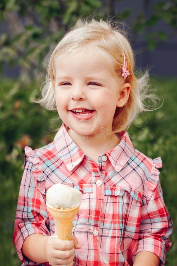 Blondes Vorschulmädchen mit blauen Augen im roten rosa Hemd essend, Eiscreme im Waffelkegel leckend stockbild