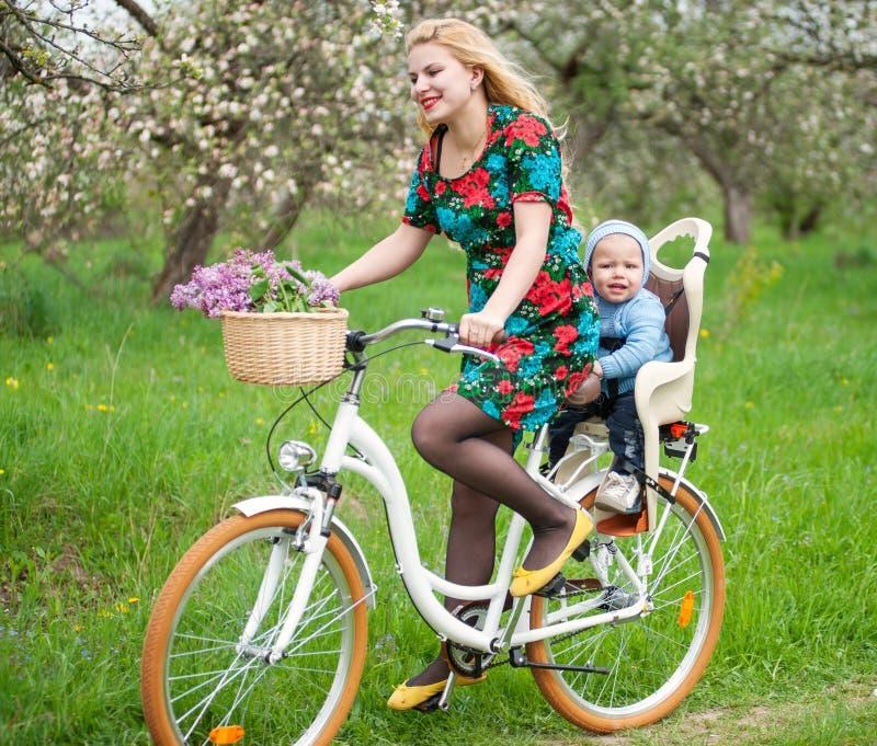 Blondes weibliches Reitstadtfahrrad mit Baby im Fahrradstuhl stockfotos