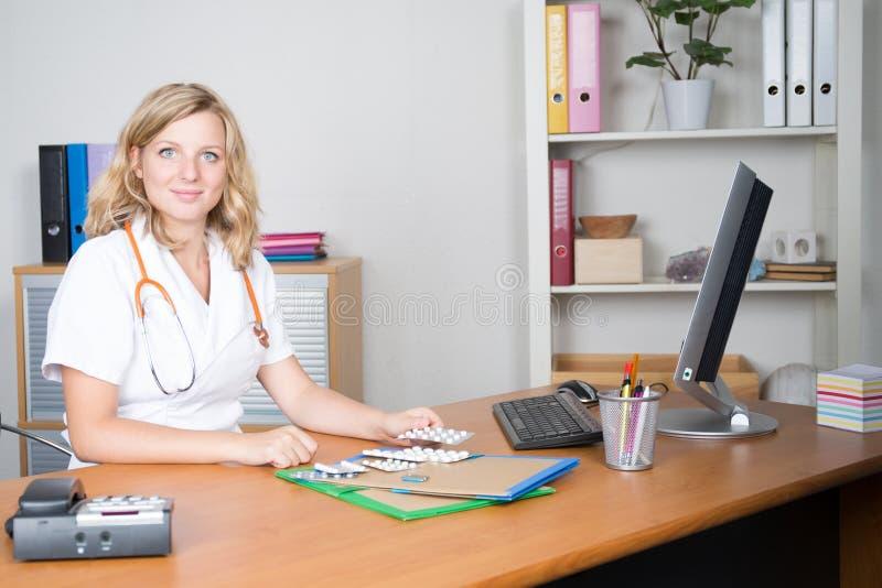 Blondevrouw artsenzitting in medisch bureau stock foto's