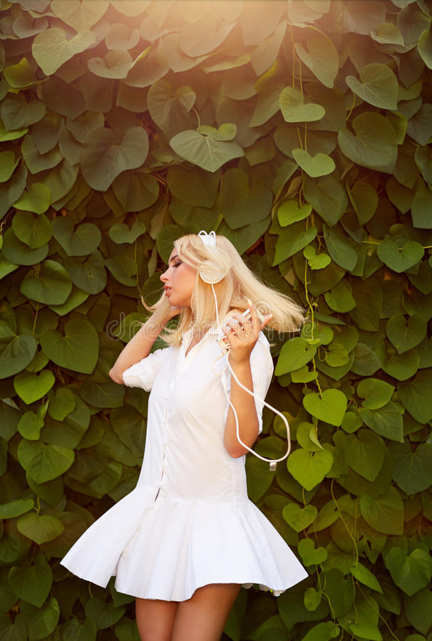 Blondevrouw die in dansen groene bladeren terwijl het luisteren aan muziek royalty-vrije stock afbeelding