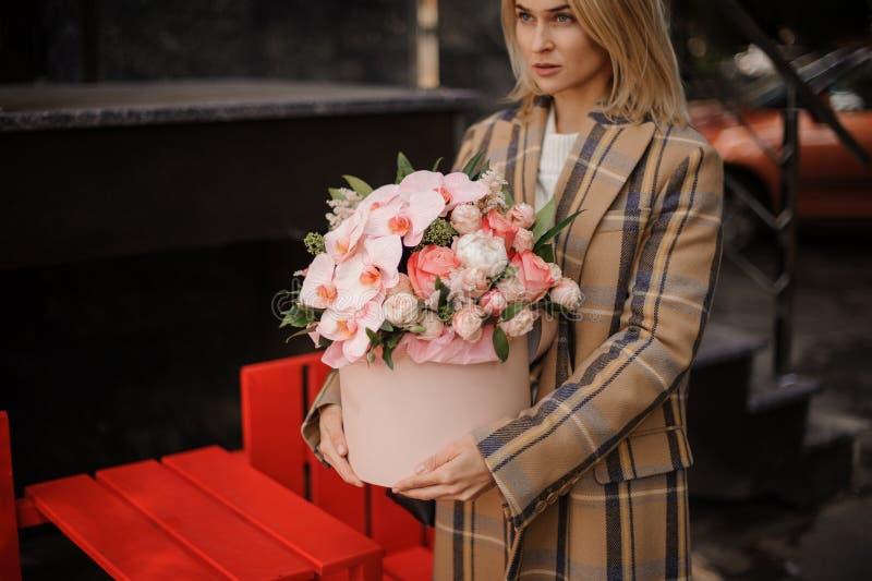 Blondevrouw die in de laag van de plaidherfst een roze doos van bloemen houden stock foto
