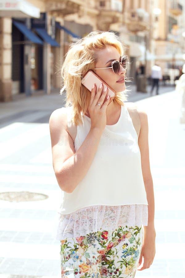 Blondevrouw die door mobiele telefoon spreken stock afbeeldingen