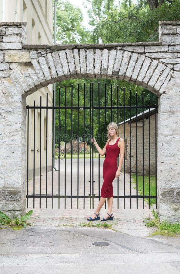 Blondevrouw die een boom in park koesteren Jong meisje in een rode kleding die die in aard rusten, tegen een boom wordt geleund royalty-vrije stock foto
