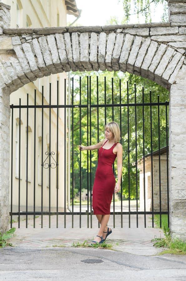 Blondevrouw die een boom in park koesteren Jong meisje in een rode kleding die die in aard rusten, tegen een boom wordt geleund royalty-vrije stock foto's