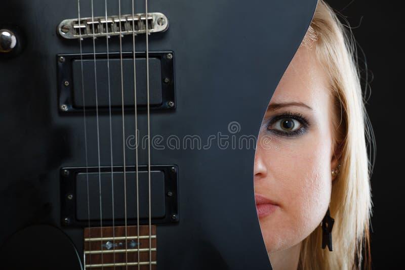 Blondevrouw die elektrische gitaar, zwarte achtergrond houden stock foto's