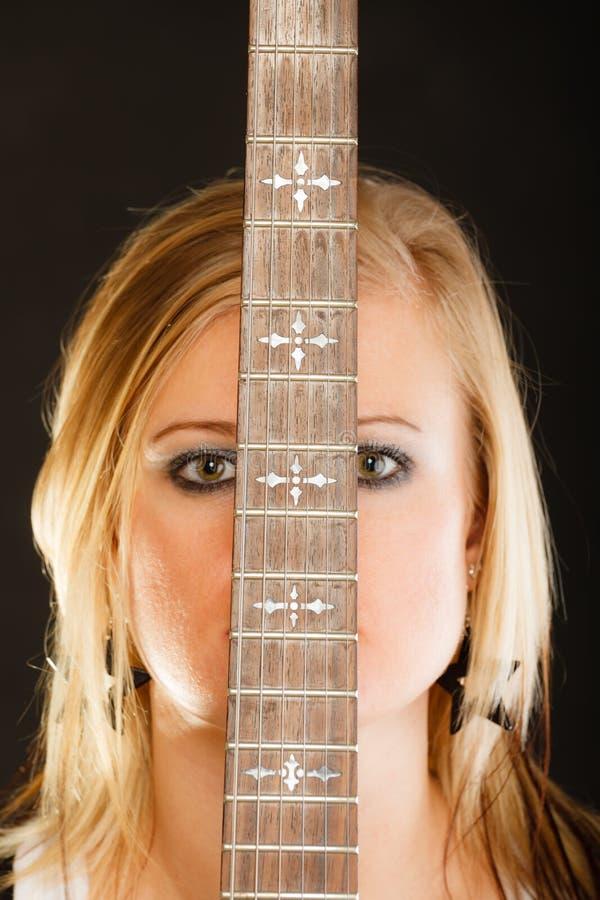 Blondevrouw die elektrische gitaar, zwarte achtergrond houden stock afbeeldingen