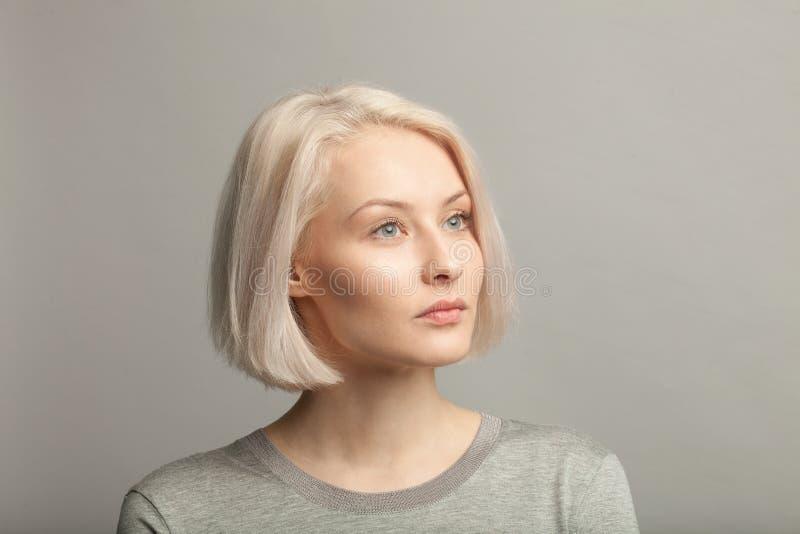 Blondevrouw die in grijze t-shirt net op grijze achtergrond kijken royalty-vrije stock afbeelding