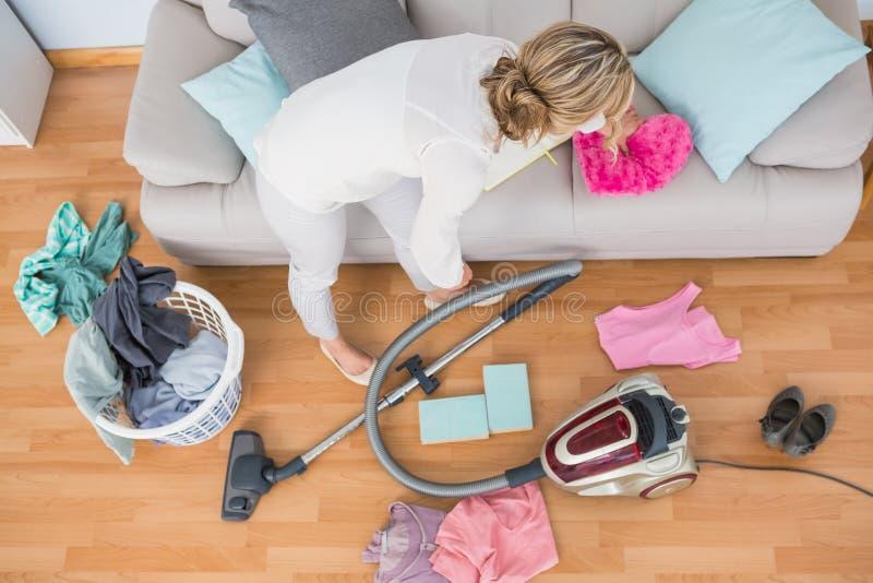 Blondevrouw die haar chaotische woonkamer schoonmaken stock afbeelding