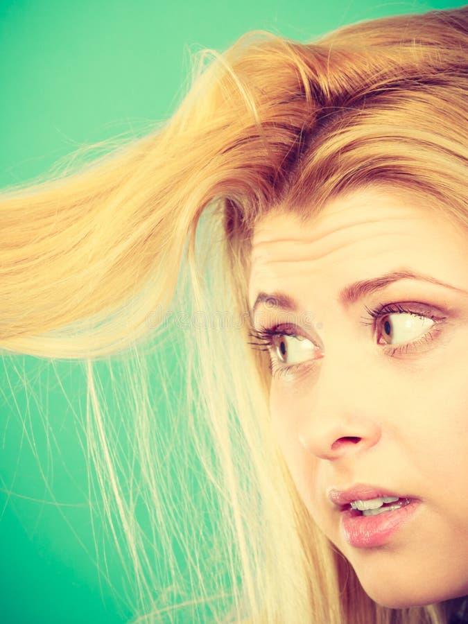 Blondevrouw die haar haareinden houden royalty-vrije stock afbeelding
