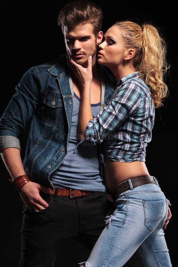 Blondevrouw die haar vriend op de wang proberen te kussen stock foto