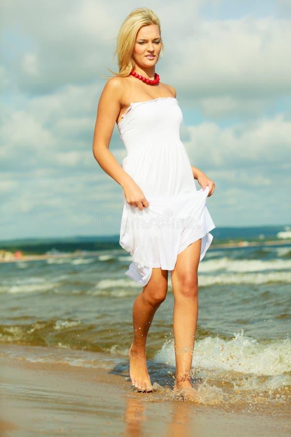 Blondevrouw die kleding dragen die in water lopen stock afbeeldingen