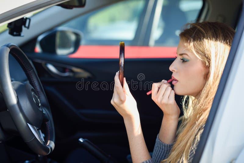 Blondevrouw die lippenstift toepassen die spiegel in haar auto bekijken royalty-vrije stock fotografie