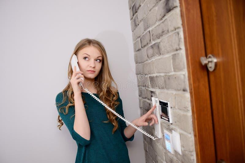 Blondevrouw die op de intercom spreken stock fotografie