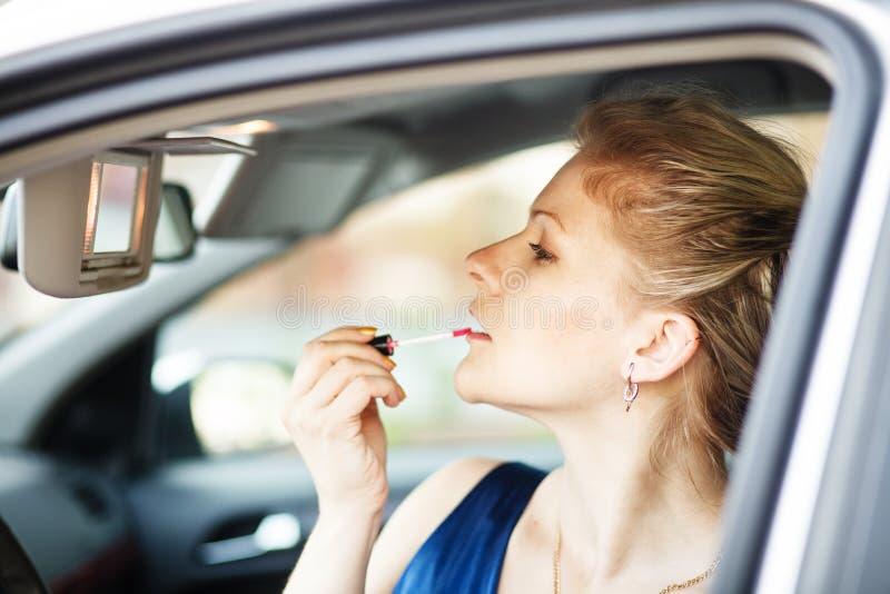 Blondevrouw die samenstelling in een auto toepassen stock foto