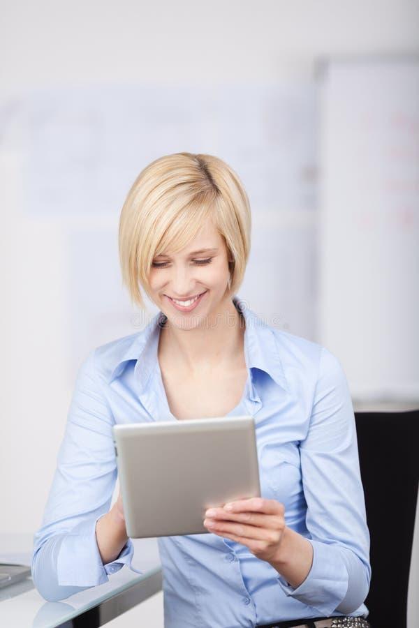 Blondevrouw die tablet-PC met behulp van royalty-vrije stock foto's