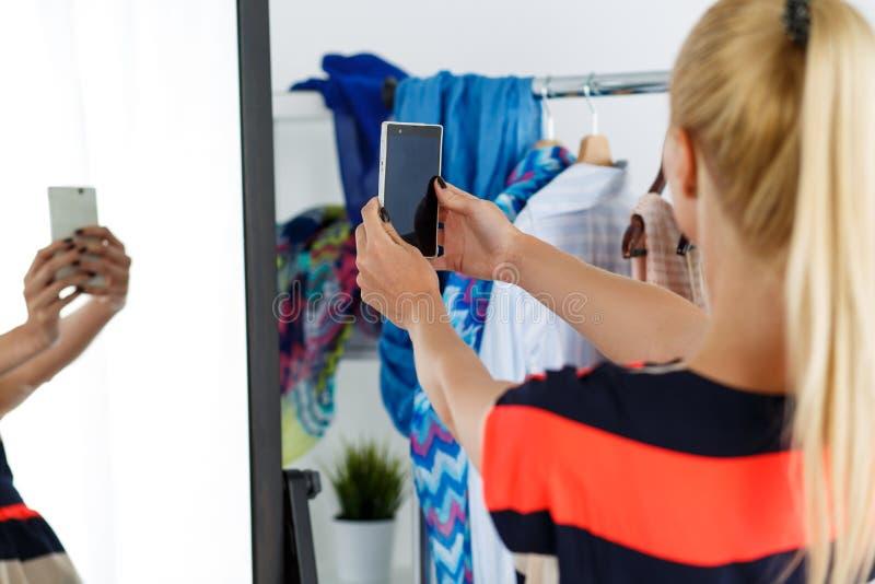 Blondevrouw die zich dichtbij het hoogtepunt van het garderoberek van kleren bevinden en mir stock fotografie