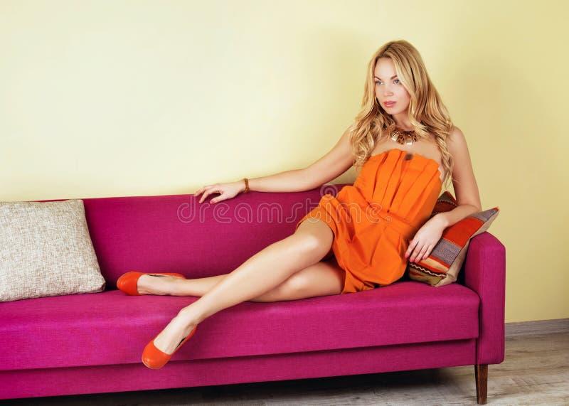 blondevrouw in een oranje kleding op purpere laag stock afbeelding