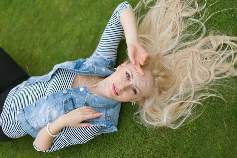 Blondevrouw het liggen op het gras met untressed haar royalty-vrije stock foto