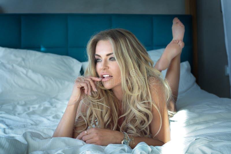 Blondevrouw het stellen in hotelruimte stock fotografie