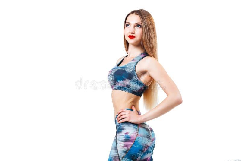 Blondevrouw in kleurenbovenkant en beenkappen die over geïsoleerde witte achtergrond stellen Sport, fitness stock fotografie