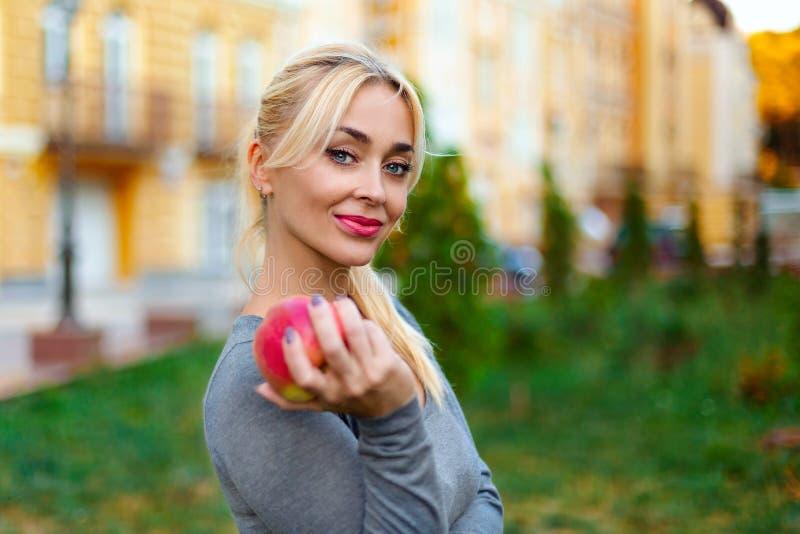 Blondevrouw met appel stock foto