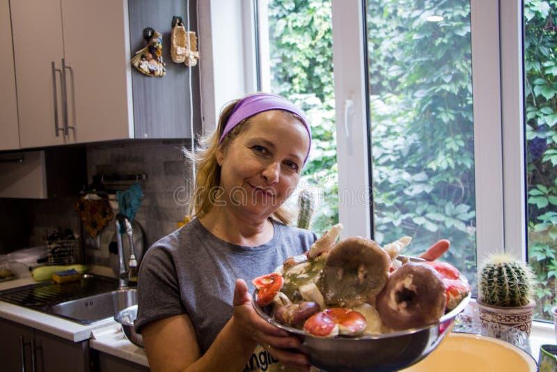 Blondevrouw met een plaat van russulapaddestoel stock foto