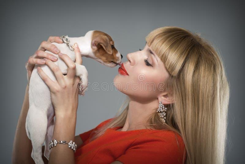 Blondevrouw met een puppy Jack Russell stock foto