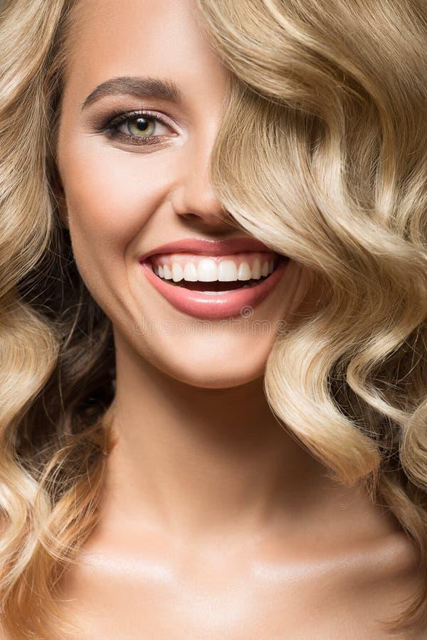 Blondevrouw met het krullende mooie haar glimlachen stock afbeelding