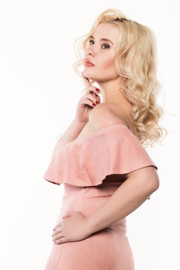 Blondevrouw met mooie krullen die op een lichte achtergrond stellen Meisje met krullend kapsel en sexy lippen stock afbeeldingen