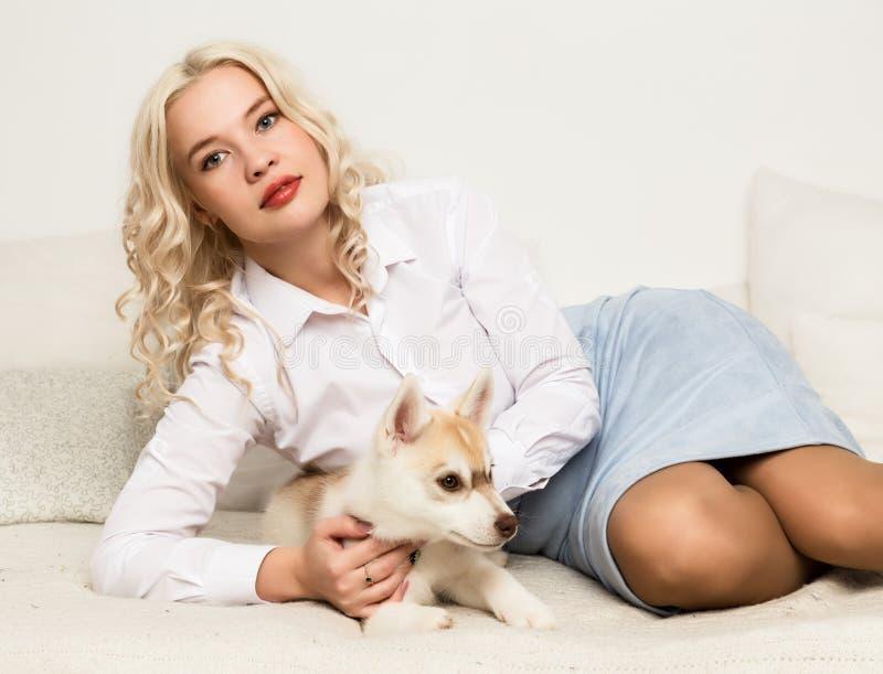 Blondevrouw met puppy schor hond op een witte bank Het spelen van het meisje met een hond stock afbeeldingen