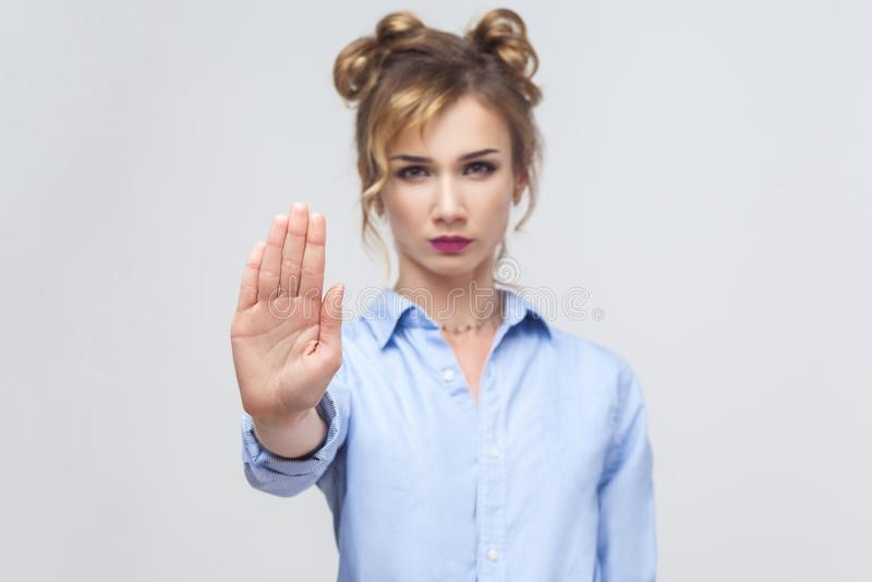 Blondevrouw met slechte houding die eindegebaar met haar palm maken stock fotografie