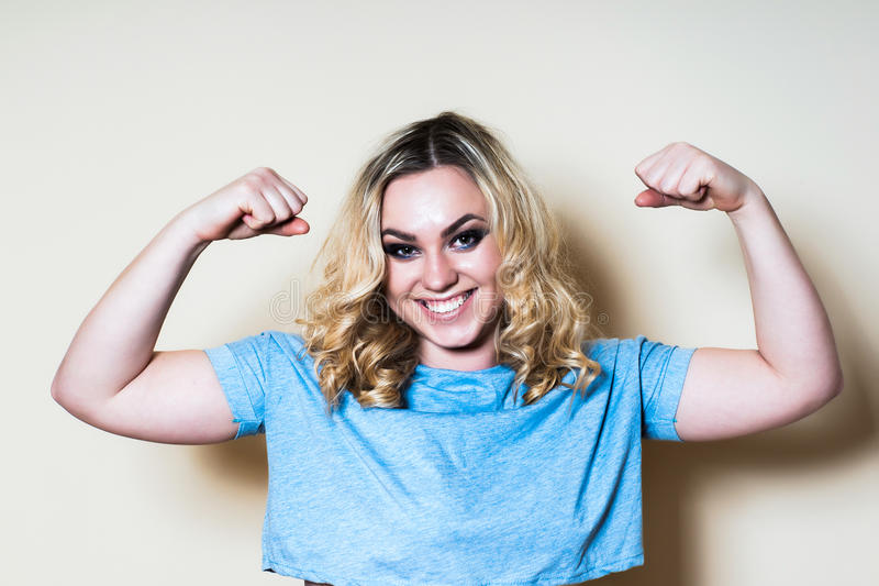 Blondevrouw op een lichte achtergrond die bicepsen tonen royalty-vrije stock afbeelding