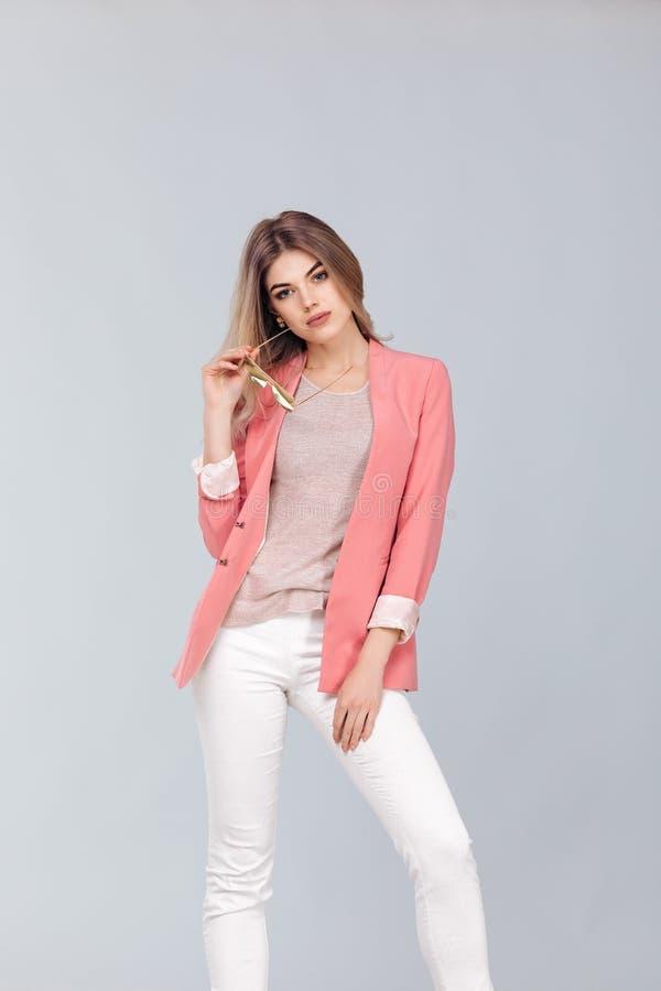 Blondevrouw in pastelkleur het toevallige jasje stellen in studio stock foto's