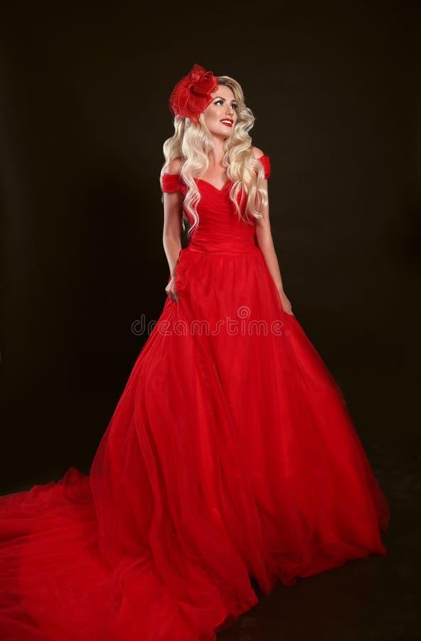 Blondevrouw in rode kleding en elegante die hoed op studiobla wordt geïsoleerd royalty-vrije stock fotografie