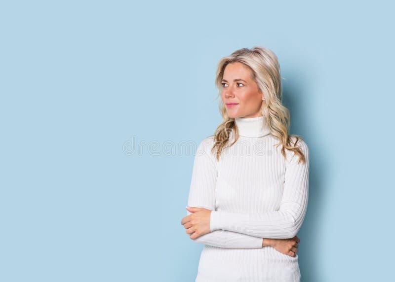 Blondevrouw volwassen aantrekkelijk mooi het glimlachen portret, Kaukasisch en Skandinavisch meisje op blauwe achtergrond stock afbeeldingen