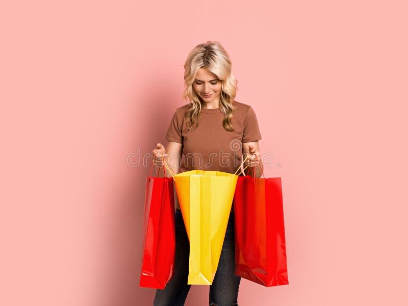 Blondevrouw volwassen aantrekkelijk mooi het glimlachen portret, Kaukasisch meisje met het winkelen zakken op roze achtergrond stock foto's