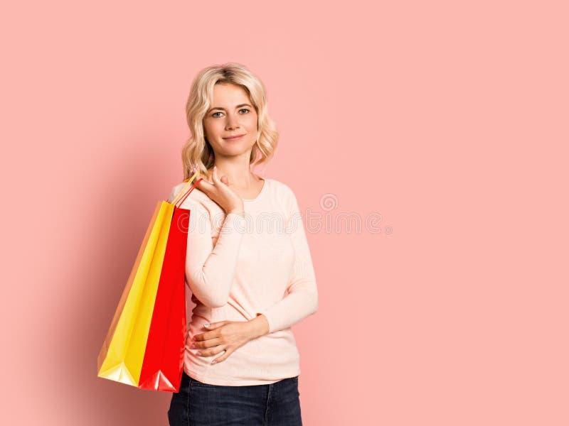 Blondevrouw volwassen aantrekkelijk mooi het glimlachen portret, Kaukasisch meisje met het winkelen zakken op roze achtergrond stock afbeeldingen