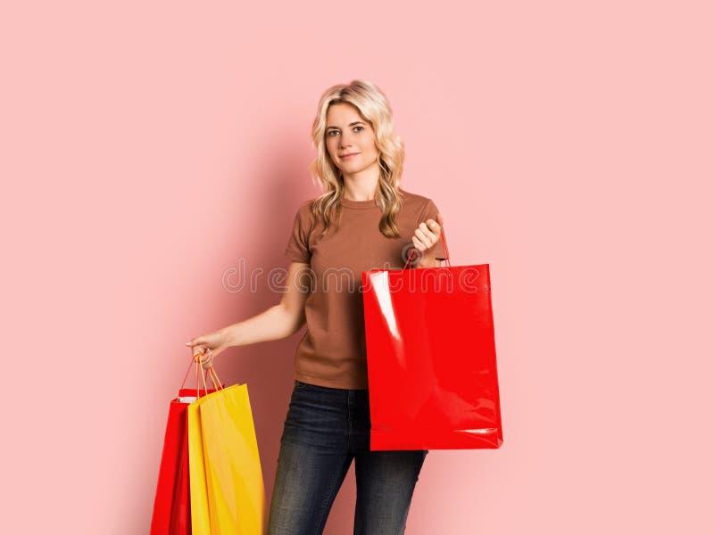 Blondevrouw volwassen aantrekkelijk mooi het glimlachen portret, Kaukasisch meisje met het winkelen zakken op roze achtergrond royalty-vrije stock afbeelding