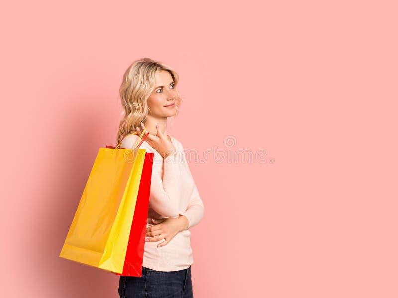 Blondevrouw volwassen aantrekkelijk mooi het glimlachen portret, Kaukasisch meisje met het winkelen zakken op roze achtergrond stock afbeelding