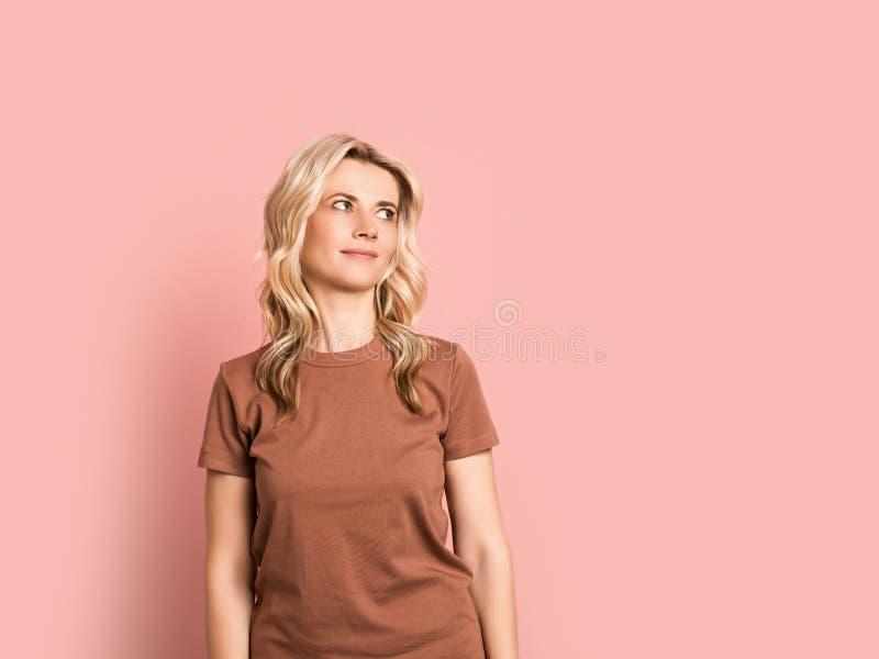 Blondevrouw volwassen aantrekkelijk mooi het glimlachen portret, Kaukasisch meisje op roze achtergrond stock afbeeldingen
