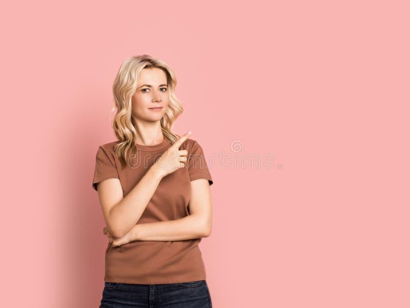 Blondevrouw volwassen aantrekkelijk mooi het glimlachen portret, Kaukasisch meisje op roze achtergrond royalty-vrije stock fotografie